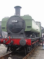"A pannier tank locomotive is seen from the front a slightly to the right. The cab and pannier tank are painted green. The chimney, smokebox, running plate, splashers, and wheels are black, and the buffer beam and coupling rods are red. The number, 7754, is shown in white letters on a black plate on the smokebox door. Part of round cab window is visible and is edged in brass. The white lettering ""NCB 7754"" is on the side of the pannier tank."