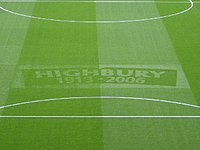A photograph of a green football turf, with the words Highbury, 1913–2006 etched in the middle.