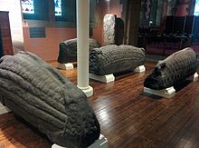 Photo of several sculpted hogback monuments