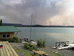 Home on lake with forest fire in background