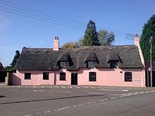 Large pink thatched cottage built on slight curve of road 5 front windows 1 front door 3 attic windows chimney No front garden