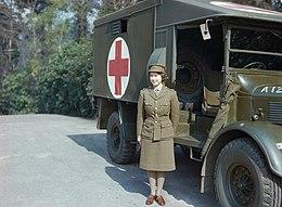 Wyprostowana młoda kobieta stoi przed samochodem wojskowym. Ubrana jest w zielony mundur wojskową czapkę i trzewiki, rajstopy w kolorze moro, spogląda w lewo i lekko się uśmiecha. Ma brązowe kręcone włosy. Na samochodzie narysowany czerwony krzyż na białym tle. Koła samochodu sięgają do bioder kobiety. Beton, w tle roślinność.