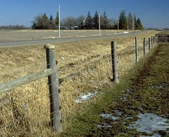 Electric fence - The wires attached to the posts with black insulators are electrified