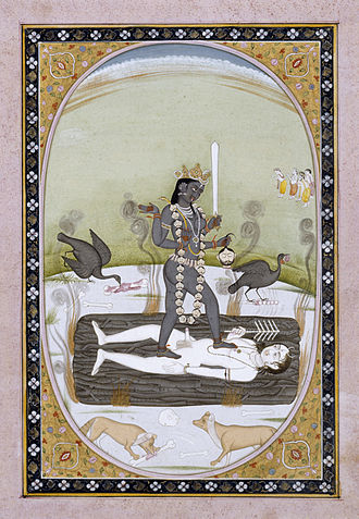 Kali - A Kangra painting of Kali stands on Shiva, who assumes the position of a corpse atop a blazing funeral pyre. Dogs and scavenger birds surround Kali.