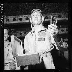 Jubilant over the success of the task force raid on Rabaul, Cdr. Joseph C. Clifton passes out cigars aboard USS... - NARA - 520765.jpg