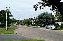 A photograph of a quiet suburban street. The houses are large and semi-detached, fronted by paved driveways and mown grass verges.