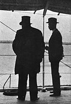 Kruger viewed in silhouette from behind, Bredell to his right. Kruger is wearing his trademark top hat.