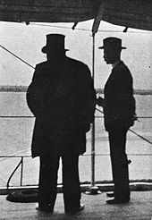 Kruger viewed in silhouette from behind, Bredell to his right. Kruger is wearing his top hat.