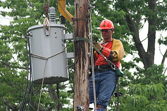 Lineworker - Lineman replacing a transformer, wearing protective gear, including rubber gloves and sleeves