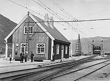 A small wooden train station building with a railway ferry in the background