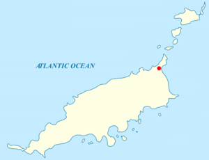 Map of an archipelago in the Atlantic Ocean. The main island is rod-shaped, oriented approximately west-southwest to east-northeast, with some irregular features in the coastline. A red label at the northeastern tip. Off the southern coast are nine smaller islands. Off the northeastern tip of the main island are five other smaller islands.