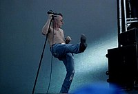 A man with a microphone stand holds his right leg into the air while facing to his left.