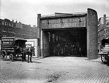 "A horse and cart stand in a street outside a narrow building with large open doors and a dark interior. A sign above the doors says ""Metropolitan Railway Goods Depot""."