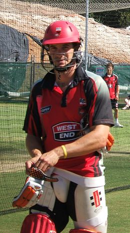 A cricketer stands in batting equipment looking at the camera