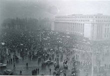 Demonstration in front of large, square building