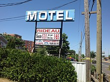 "Sign at Motel Rideau, 8700 boulevard Marie-Victorin, Brossard, Quebec, advertising ""siesta"" and overnight rates."