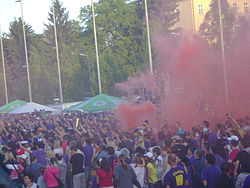 Hundred of fans, wearing purple, celebrating with purple smoke from flares in the background.