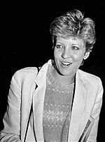 Photo noir et blanc d'une femme blonde aux cheveux courts, pommette marquées, qui parait souriante et vive