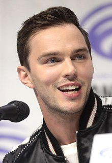 A young, Caucasian man with short, dark hair and facial stubble wearing a black shirt looks away from a microphone against a grey and blue background.