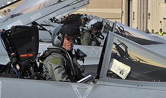 A row of helmeted pilots in the cockpits of their fighter jets
