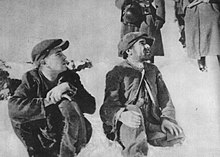 Two men in caps, sitting in the snow