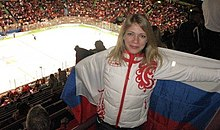 A woman with shoulder-length blonde hair is wearing a white jacket with a red pattern. She is hold a Russian flag behind her back with white, blue and red horizontal stripes. Below her is a horizontal ice rink and a large group of seats is surrounding it from all sides, some with spectators occupying them.