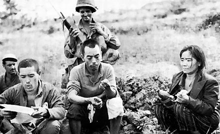 Two surrendered Japanese soldiers with a Japanese civilian and two US soldiers on Okinawa. The Japanese soldier on the left is reading a propaganda leaflet. Overcoming the last resistance.jpg