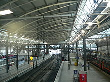 The interior of a large modern railway-station with a curved roof and skylights. An Inter-City train is at Platform 9c to the right and a local train is at one of the platforms on the far left. In between, three empty tracks with crossovers can be seen between the curved platforms 11 and 12, both of which have low modern buildings for passenger use and gantries for signals and overhead cables. A footbridge with escalators can be seen at the far end of the station, and some of the platforms extend further outside the overall roof.