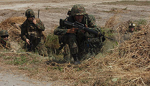 Philippine Marine Corps - A Philippine marine rushes up a small ditch while a U.S. Marine provides communication during the Balikatan Exercise