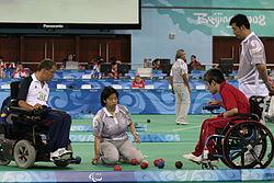 Dois atletas em cadeira de rodas estão frente-a-frente, ambos olhando para o chão, onde estão as bolas usadas no esporte. Uma juíza está agachada entre eles e outro observa em pé, ao fundo.
