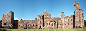 A sandstone castle-like building with a tower slightly to the left of centre. The walls are battlemented and in the foreground is a grassed area