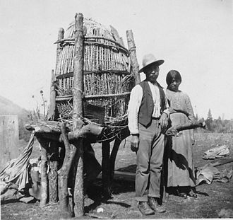 Mono people - Mono Indians stand beside their Acorn cache in Fresno County, California, ca. 1920. Mono Indians used Acorns for their bread and families typically have 8 or 9 baskets of this size with acorns.