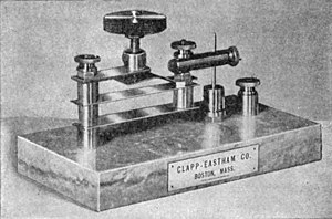 "Cat's-whisker detector - Precision cat's whisker detector with iron pyrite crystal, used in large wireless stations, early 1900s. The crystal is inside the metal capsule under the vertical needle ""whisker"" (right).  The leaf springs and thumbscrew allowed fine adjustment of the pressure of the needle on the crystal."