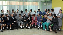 Color image of President Piñera visiting the rescued miners who are dressed in hospital robes and pajamas while seated and standing in a semi-circle in a hospital room