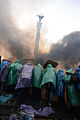 Protesters holding protective positions behind an improvised wooden shields right in the middle of the Central Square, Independence Monument is seen on the background, covered with smoke. Clashes in Ukraine, Kyiv..jpg