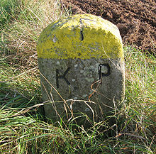 "Weathered, lichen-covered stone standing in a field with ""K.P."" carved on one face"
