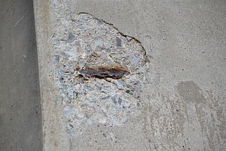 Concrete degradation - Example of flat piece of concrete having dislodged with corroded rebar underneath, Welland River bridge across Queen Elizabeth Way in Niagara Falls, Ontario.