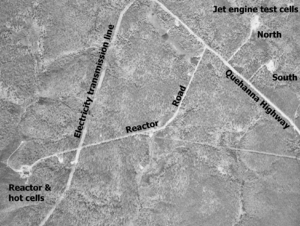 "Black and white aerial view of several roads through a forest with a few buildings. The image is labeled ""Jet engine test cells"" in the upper right corner with buildings in two cleared circles at end of small roads labeled ""North"" and ""South"". In the lower left corner is a larger building in a cleared area labeled ""Reactor & hot cells"". The road to this is labeled ""Reactor Road"" and it leads to the labeled ""Quehanna Highway"". A clearcut strip is labeled ""Electricity transmission line""."