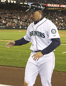 "An olive-skinned man in a white baseball uniform with ""Mariners"" across the chest and a dark baseball cap"
