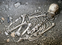 A disarticulated skeleton in a gravelly pit