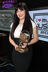 Velasquez holding a trophy for an award she has won