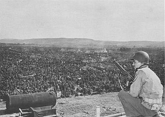 Rheinwiesenlager - A U.S. soldier at Camp Remagen guarding thousands of German soldiers captured in the Ruhr area in April 1945.