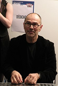 Head and shoulders portrait of sitting 60-year-old man in rimless glasses, black suit, and black tee-shirt, with both hands lying on a table.