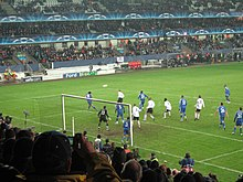 White and blue players standing inside the penalty area during a corner kick