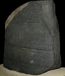 """A large, dark grey-coloured slab of stone with text that uses Ancient Egyptian hieroglyphs, demotic and Greek script in three separate horizontal registers"""