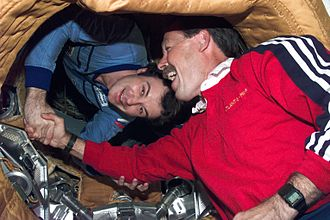 STS-71 - Russian and American astronauts shake hands in orbit, an homage to ASTP