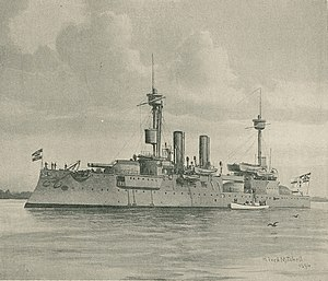 A large gray warship with two tall masts and two thin smoke stacks sits motionless offshore