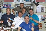 STS-112 and Expedition 5 crew share a meal
