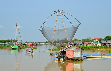 Fishing boat at Sangker river with Svang floating village in background, Cambodia.