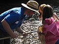 Service biologist Bryan Tompkins helps two students look for aquatic macroinvertebrates (5029129193).jpg